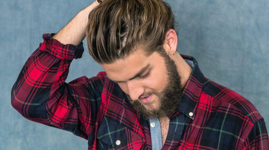 Young Man Adjusting Hair Bun